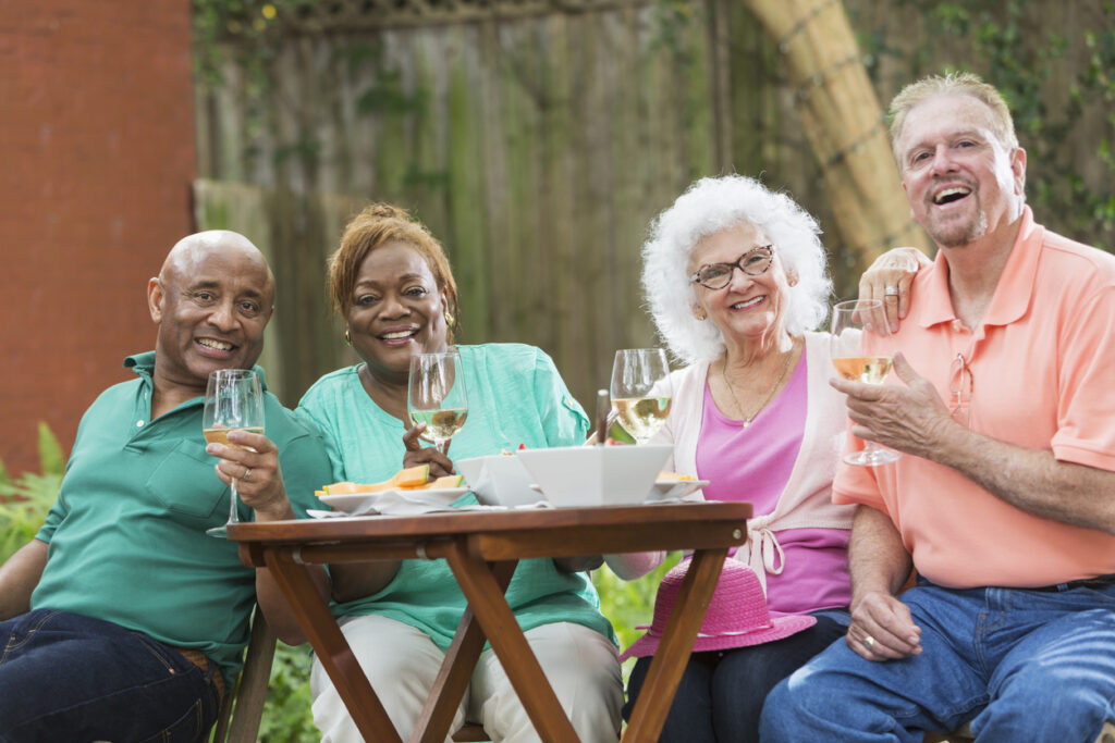 Group of seniors enjoying wine and food in back yard