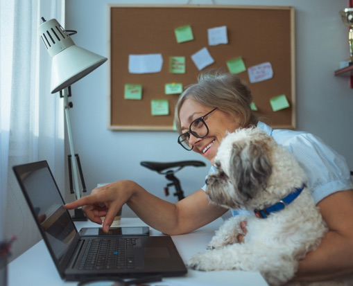 Woman smiling, holding dog, and pointing to laptop